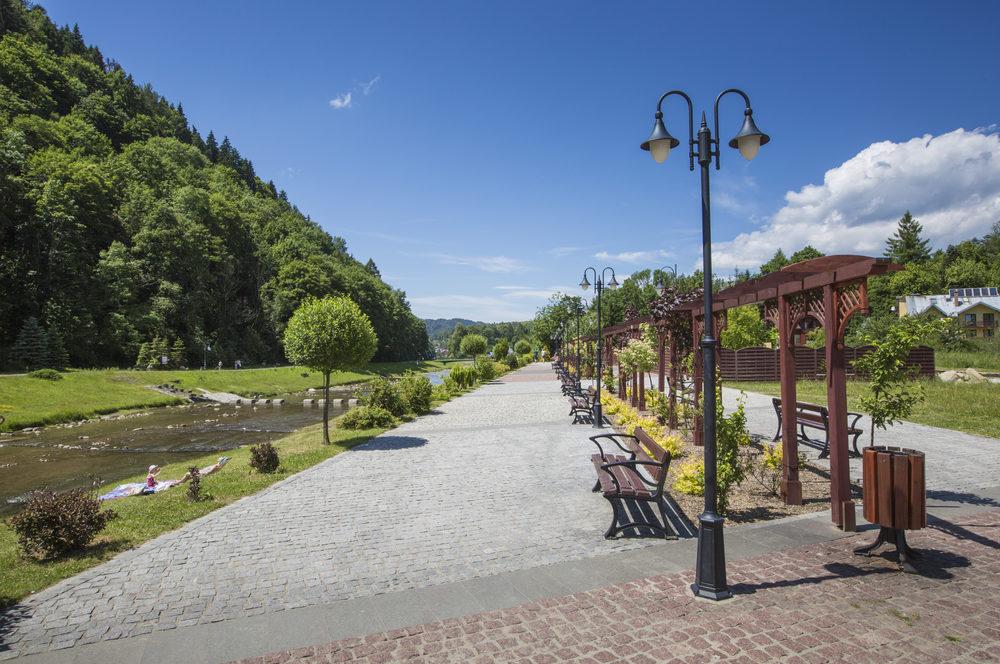 Promenade along a river Szczawnica village on sunny summer day, Beskid Niski Mountains, Poland
